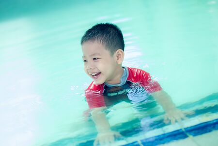 The Asian boy swimming suit has fun at the pool. Portrait of cute little Asian child. Stockfoto