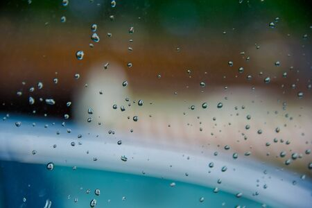 Drops of rain on glass with green tree nature background,romantic shot scene content,colorful raindrops.Blurred leaves of trees.