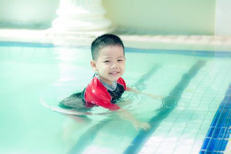 The Asian boy swimming suit has fun at the pool. Portrait of cute little Asian child