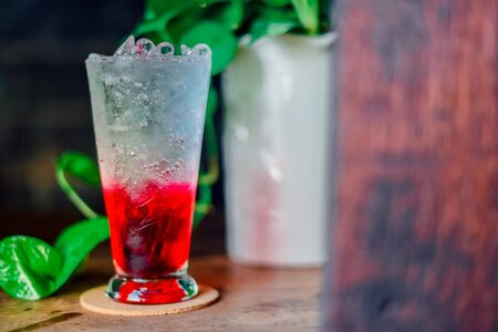 red juice water whit soda in glass on wood table at cafe. Summer  drink