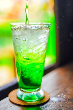 green juice water whit soda in glass on wood table at cafe. Summer  drink