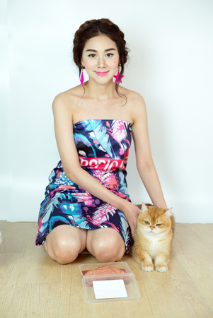 Beautiful women with cats eating cat food