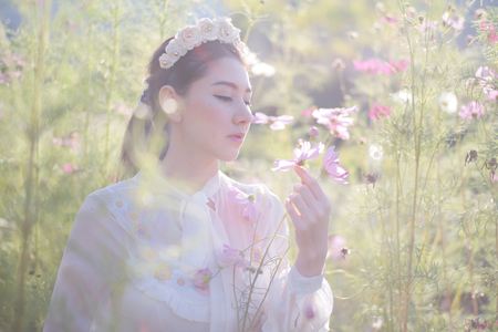 Beautiful girl With a field of flowers cosmos on a sunny day