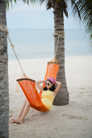 Beautiful woman lying on the cradle at the beach by the sea.