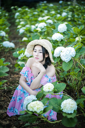 Beautiful girl wearing a pink hat with a field of flowers Hydrangea.