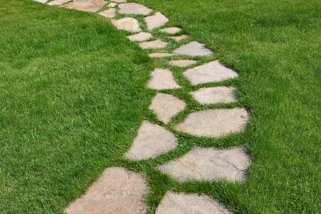 Steenweg op een groen grasrijk gazon. De manier verharde enige stenen onder een groen gras. Stockfoto - 81209431