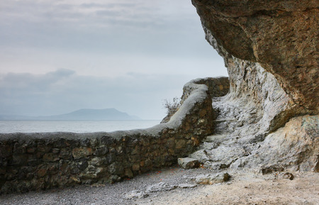 scarp: Crimean landscape on a cloudy day. The path leading to the grotto Chaliapin, and views of the Cape Meganom on the horizon. Novy Svet, Crimea.