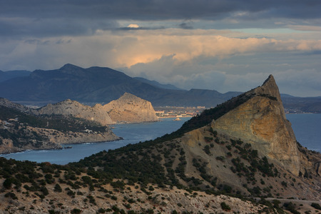 Landscape of Crimea. Scenic views of the coastline with rocky cliffs and storm clouds during sunset. Novy Svet and Sudak.
