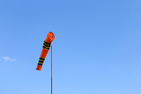 Wind cone against blue sky. Windsock in windless and perfect flying weather. Фото со стока