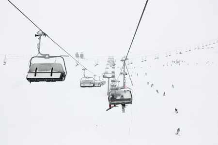 Ski season in the Alps. Panorama of the ski lifts during snowfall and fog. Picture taken in Austrian Alps. Stock fotó