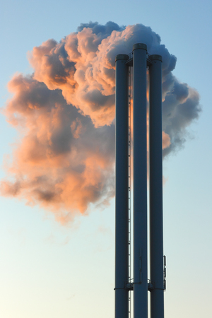 steam output: Emission into the environment of steam coming out of factory chimneys. Dense cloud of smoke in the red light of the sunlight. Stock Photo