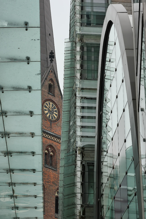 collation: Unusual cityscape of Hamburg. View of the St. Peters church through the elements of a modern building.