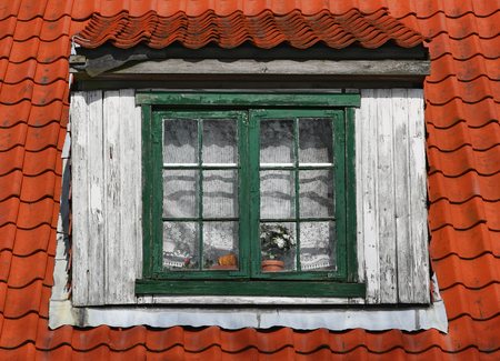 Old window of attic. Window with a wooden frame on a tile roof. Stock Photo