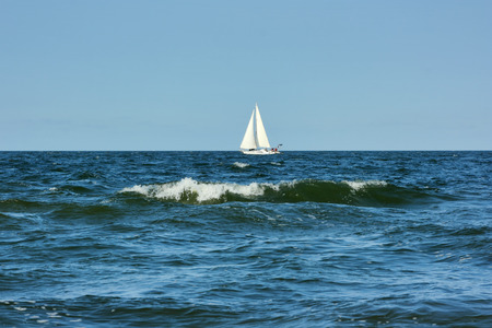 Sailing boat in the sea in windy weather.