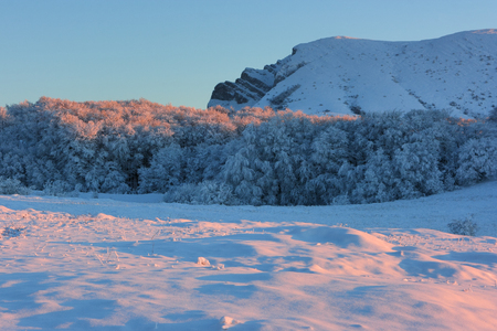 Sunset colors at mountain plateau in winter. The Chatyr-Dag mountain in Crimea at evening time. Stock Photo