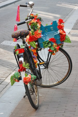 Fietsen van Amsterdam. Geparkeerde fiets met plastic heldere rode bloemen. Stockfoto