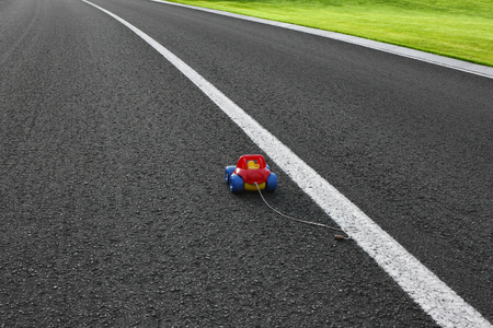Toy on the road. Baby car on the motorway.