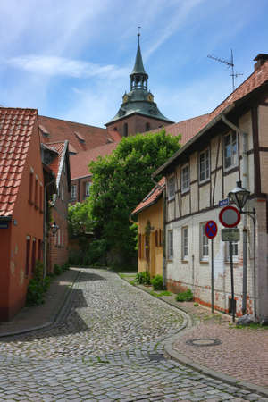 Vintage street in Luneburg, Lower Saxony, Germany. The ancient traditional architecture and the tower of the church of St. Michaelis in Luneburg. Stock fotó