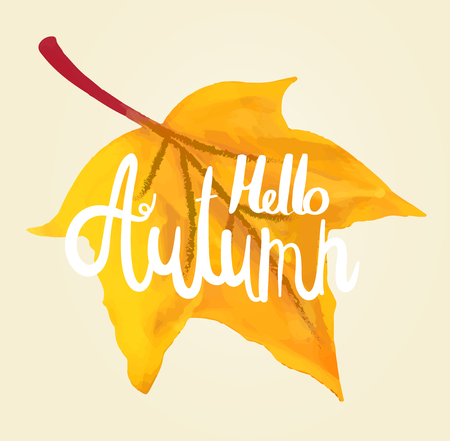 Hello autumn calligraphy by hand on a maple leaf made with watercolor