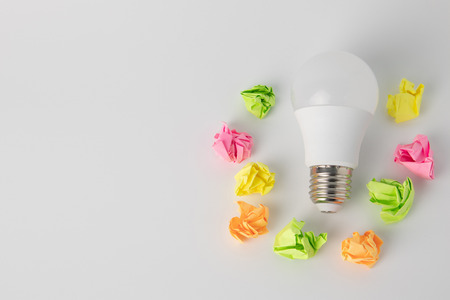 multi-colored sticky notes crumpled papers ball Light bulb on white background office concept no idea