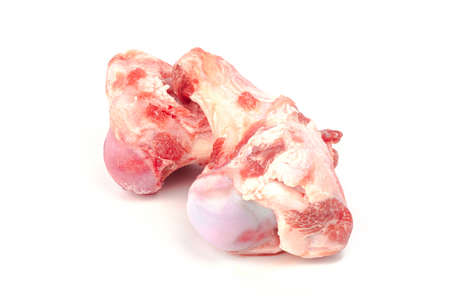 Close up frozen fresh pork bones with red meat stuck To be used for making pork bone broth on a white background Archivio Fotografico