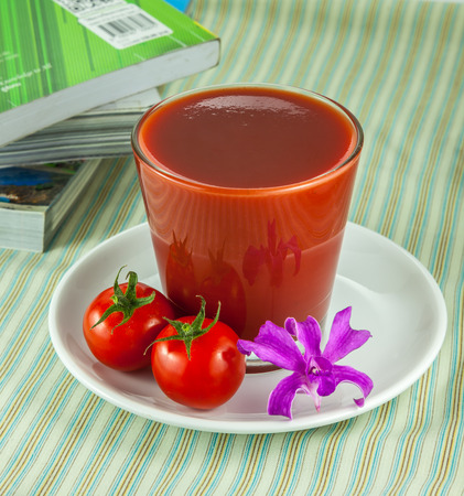 jugo de tomate: Jugo de tomate en vidrio y tomates frescos en la mesa
