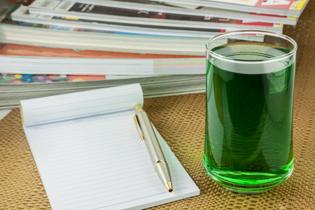 chlorophyll: chlorophyll  in glass and notebook on  Brown tablecloth