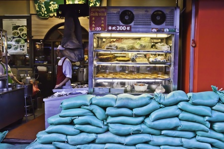 BANGKOK - NOVEMBER 3: The famous Chinese restaurants in Chinatown of Thailand is alert to the possible flood attack by equipping the sandbags arrays in front of the shop. Editorial