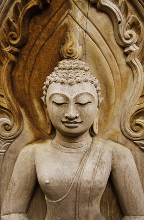 The wooden Buddha statue is smiling with mercy. photo