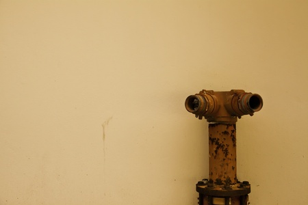 The old red water hose is among the yellowish plain wall. Stock Photo - 11193602
