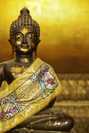 The golden black buddha statue in the setting posture. photo