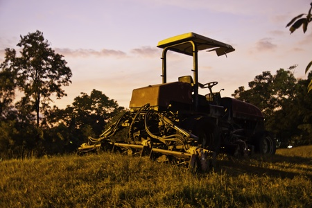 The yellow tractor in the field of beautiful sunset landscape. Stock Photo