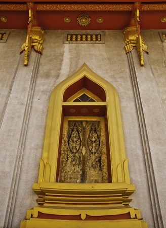 The golden window of the Thai temple architecture is marvelous painted and decorated. photo
