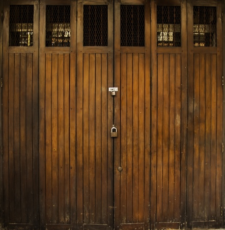 The grougy old style door at the shophouse in Bangkok Thailand. photo