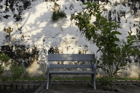 The old bench is at the grungy wall on the side of the street. It makes us feel so serene when sitting here.