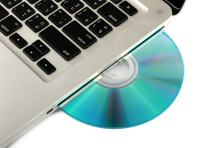 optical disk: DVD, CD disk in the drive of a laptop white background, close-up, isolated