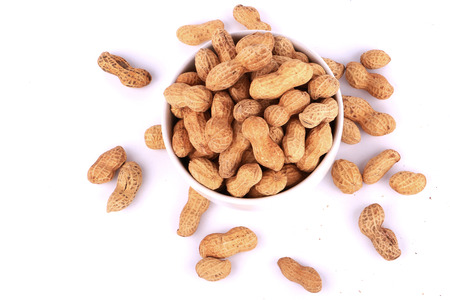 monkey nuts: Monkey nuts, peanuts or groundnuts in shells, isolated on a white background in cup Stock Photo