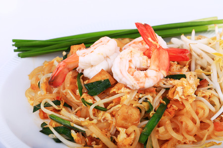 padthai: Fried noodle Thai style with prawns, Stir fry noodles with shrimp in padthai style on table. Front view isolate white , brown background Stock Photo