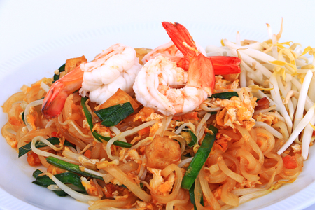 asian noodles: Fried noodle Thai style with prawns, Stir fry noodles with shrimp in padthai style on table. Front view isolate white , brown background Stock Photo