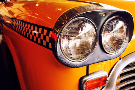 old sign: Yellow Cab Taxi, Color detail on the headlight of Taxi Checker