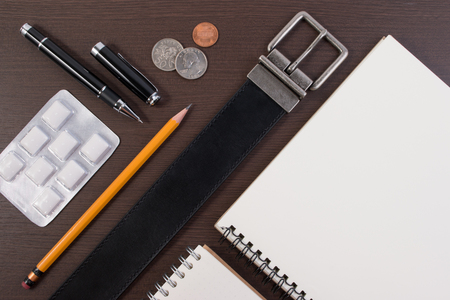 chewing gum: Flat lay top view business concept. Accessory belt with pen, notebook and chewing gum on wooden table.
