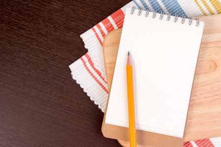 recipe background: Notebook for culinary recipes on a cutting board with napkin. Open recipe book on wooden background.