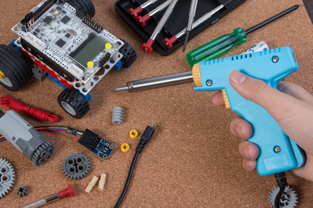 Hand holding soldering iron tool assembling robot with microcontroller. Stock Photo
