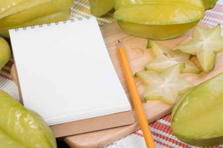 Star apple or averrhoa carambola and notebook on wooden block. Fresh star apple fruit and on wood table.