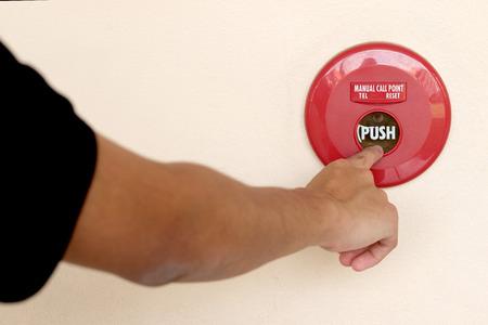 closeup shot of human hand pushing fire alarm. The hand of man is pushing fire alarm switch on the wall.