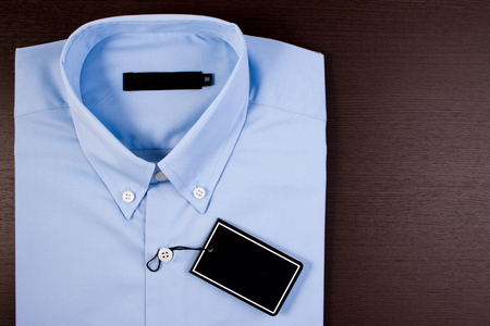 Blue shirt on wooden background. Blue shirt with black blank price tag.