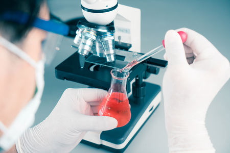 Hands of young Asian man and white microscope in science laboratory with red liquid and dropper for testing. Technician dripping red water on slide glass in science lab.