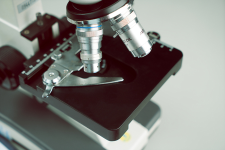 Close up of old vintage of microscope with metal lens and science equipment at laboratory research desk. School laboratory and classic microscope for students. Banco de Imagens