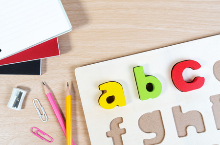 Close up of alphabet board game and basic equipment for elementary student. Wooden ABC alphabet game concept.