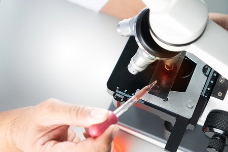 Young Asian student boy and white microscope in science laboratory with red liquid and dropper for testing. Technician dripping red water on slide glass in science lab.